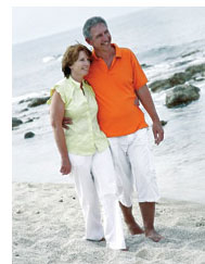 Healthy middle aged couple walking on the beach